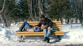 tükenme : Man and a woman rest together on a bench in the winter city Park. Sunny winter day. Stok Video