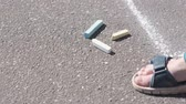 kreda : Boy takes chalk from asphalt and goes to paint. Close-up hand. Wideo