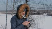 başlık : Woman in a blue down jacket with a fur hood writes messaging in her cellphone in a winter Park. Stok Video