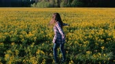pradaria : Brunette woman is spinning in the middle of a field with yellow flowers.