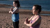 tilt : Two woman stretching yoga standing on the beach by the river in the city. Beautiful city view. Namaste pose.