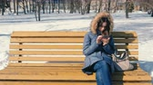 プロバイダー : Woman is browsing internet on her phone sitting on the bench in winter city park in sunny day. 動画素材