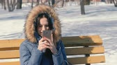 プロバイダー : Woman types a message on her phone sitting on the bench in winter city park in sunny day.