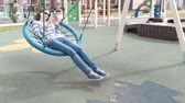 palmado : Woman is swinging on empty webbed swing and typing a message on mobile phone.
