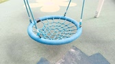 palmado : Blue empty webbed swing in playground. Vídeos