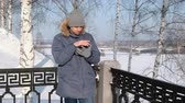 Man in blue down jacket with fur hood using his cellphone for web in a winter Park. Dostupné videozáznamy
