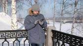 Man in blue jacket with fur hood wipes the phone screen with his hand in gloves in a winter Park. Dostupné videozáznamy