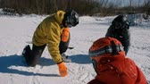 Snowboarding teacher explains to the students the technique of snowboarding, drawing diagrams on the snow. Stock Footage