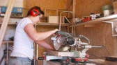 igual : Woman sawing a wood board with a circular saw.