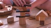 Woman is building a tower from wooden blocks. Close-up hands.
