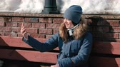 Woman is talking on video chat on mobile phone sitting in winter park.