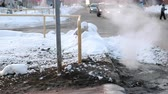 arıza : Sanitary sewer cover in snow with steam, accident. Side view.
