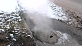 culpa : Steam is from sanitary sewer cover in snow on the roadside. Top view.