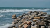 stabilita : Wall of stones on the sea shore beach.
