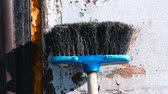 kitchen brushes : Broom against the wall with peeling plaster.