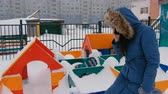 multistory : Mom calls on a mobile phone while her son walks on the playground in the winter during snowfall. Stock Footage