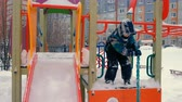 multistory : Boy plays on playground in winter.