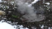arıza : Steam is from sanitary sewer cover in snow, accident. Melted snow around. Close-up view.