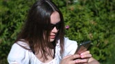 texting : Woman is typing a message on mobile phone sitting in park in sunny day, chatting.