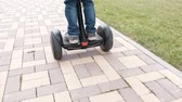 pave : Unrecognizable boy is rolling on gyro scooter near the home. Back view. Legs close-up. Stock Footage
