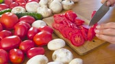 меню : Womans hands is cutting tomatoes on the wooden bord on kitchen table. Side view. Стоковые видеозаписи