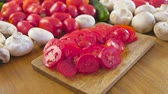 turp : Close-up view of fresh vegetables and cutting tomatoes on wooden board on kitchen table. Camera rotate.