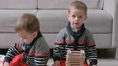дошкольник : Twins boys brothers are building from wooden blocks sitting on the floor by the sofa in their room.