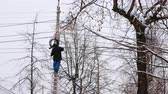 hidro : Man repair of power lines in the city in winter. Stands on a ladder with a wire in his hands, back view.