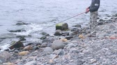 fishing rod : Unrecognizable Man is fishing rod on the sea beach. Stock Footage