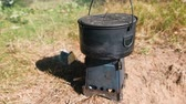 fornalha : Pot on a metal camp furnace stove on woods outdoors. Vídeos