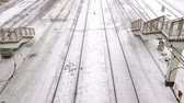 dondurucu : Railways in snow in train station among the stairs, top view, camera move ahead.