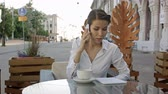 mobility : Portrait of young business woman sitting relaxed at outdoor cafe drinking coffee and calling her cell phone