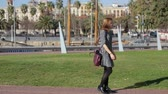 somebody : Young female in a dress with red handbag on the background of the barcelona marina park walking with smartphone and meet somebody