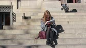 assentado : Woman sitting on the stairs and sees the tourist map