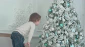 приукрашивание : Little boy sticking his tongue out at his own reflection in the bauble on the Christmas tree
