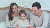 prohlížení : Happy family and son watching tablet on the sofa