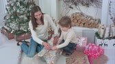 papel de embrulho : Little boy and a young mother preparing Christmas presents
