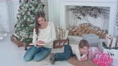 lovable : Mother reading a book for her little son lying near Christmas tree Stock Footage