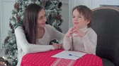milovaný : A happy boy and his mother fantasizing what to write in a letter to Santa Dostupné videozáznamy