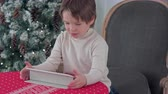 rena : Cute little boy using tablet while sitting on a big armchair at home over Chirstmas tree background