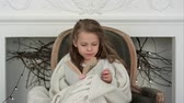 poltrona : Lovely little girl wrapped in white Christmas blanket exploring a book sitting in an armchair near the decorated fireplace