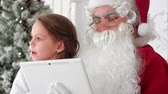 carefully : Santa Claus taking Christmas selfie on tablet with cute little girl sitting on his lap