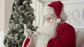 senhor : Laughing Santa Claus reading Christmas messages from kids