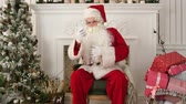 сотовый телефон : Serious Santa Claus checking his Christmas mail on the phone