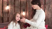 good time : Happy mother combing her daughters hair