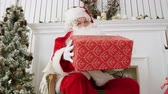 kind : Santa Claus looking at the camera and teasing with a present