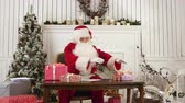 papai noel : Santa Claus arranging presents on his table
