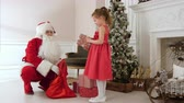 sack : Santa Claus giving presents to a pretty little girl and hugging her