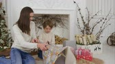 papel de embrulho : Cute little boy helping his mother to cut paper for wrapping up Christmas presents
