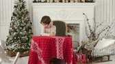 discagem : Cute little boy calling Santa while sitting on a big armchair at home over Chirstmas tree background Stock Footage